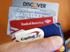 Steve Wheelock holds up his Discover Card along with his American Express, Bank of America and Capital One Visa credit cards in San Francisco, June 22, 2011.