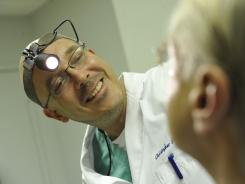 Dr. Christopher Mesick, an otolaryngologist, or ear, nose, and throat doctor, examines a patient in Washington, D.C., in December 2010.