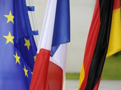 The EU, the French and the German flag flutter in the wind on July 20, 2011 in the courtyard of the Chancellory in Berlin, prior to a visit of the French President Nicolas Sarkozy for talks with German Chancellor Angela Merkel.