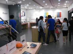Employees wearing Apple's trademark blue T-shirts talk to customers at a questionable  Apple store in Kunming, in southwest China's Yunan province, July 20, 2011.