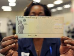 A Treasury employee in Philadelphia holds a blank U.S. Treasury check.