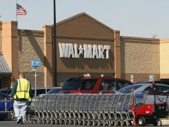 A worker gathers shopping carts near a Wal-Mart store in Washington Township, N.J.