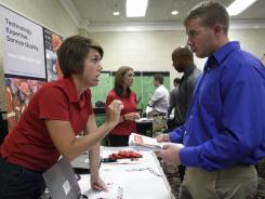 Halliburton human resource reps Heather Hopkins, left, and Sonja Franks, center rear, meet attendees at a job fair this month in Dallas.