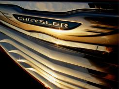 The setting sun is reflected in the grill of a Chrysler at a dealership in Springfield, Ill.