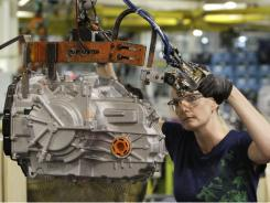 Cheryl Simpson moves a transmission from the assembly line to a pallet at the Ford Van Dyke Transmission Plant in Sterling Heights, Mich.