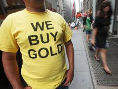 "A worker wears a ""We Buy Gold"" shirt in Manhattan. Rising gold prices have prompted many to try to cash in."