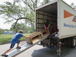 Jacob Whitehead, left, and Isaac Huber, center, load a piece of furniture onto a moving truck with Todd Dowd, right, on June 7, 2011.
