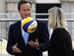 British Prime Minister David Cameron plays with a volleyball during a visit to the beach volleyball site for the 2012 Olympics, at Horse Guards Parade in central London.