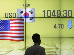 A man walks past a screen showing the exchange rate between the U.S. dollar and the South Korean won in Seoul, South Korea, Monday, Aug. 1, 2011.