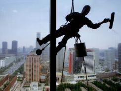 A window washer works on a Beijing office building in 2007.
