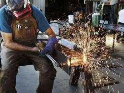 John Rosas, an employee with the metal works factory Wizard of Metals, cuts steel in San Francisco, on July 1, 2011.