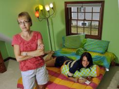 Lyz Igras, 23, and her mother, Carlene Igras, pose at their Bath, N.Y., home with items purchased five years ago when Lyz went away to college. Today, the Igras' have no use for the octopus lamp and dorm-sized matching bed set.