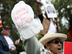 Health care costs are creating economic hardship for more seniors of color. A protestor holds an adult diaper during a rally to protect federal health programs at the 8th Annual Healthy Living Festival in Oakland, California.
