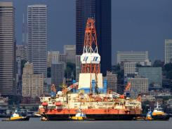 "One of Shell's floating oil-drilling platforms, ""Kulluk,"" passes downtown Seattle while being moved by tugs to a maintenance facility on July 19, 2011."
