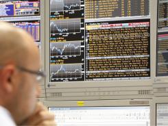 Running away:  A trader checks monitors at a bank in Milan on Monday