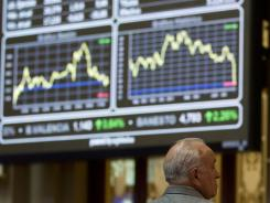 A broker looks on in front of the main screen at the Stock Exchange in Madrid on Aug. 8, 2011.