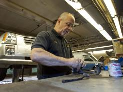 Phillip Weir works on a brake part for a 2005 Cadillac SRX in Wilmington, Del. A growing number of Americans struggle to keep their cars on the road, as job losses, furloughs and gas prices take huge bites out of their wallets.