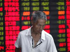 An investor looks at the stock price monitor at a private securities company Tuesday in Shanghai.