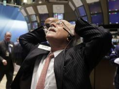 Trader Peter Tuchman works on the floor of the New York Stock Exchange as volatility continues to haunt the market.
