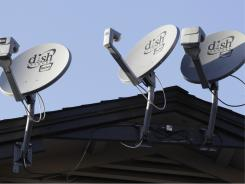 Three Dish Network satellite dishes, attached near the roof line of an apartment complex, are displayed in Palo Alto, Calif., on Feb. 23, 2011.