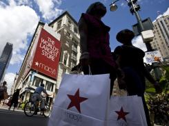 Shoppers carrying bags cross Broadway near Macy's in New York, on Aug. 9, 2008.