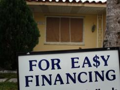 A sign advertising easy financing stands in front of a home for sale on February 11, 2011 in Miami.