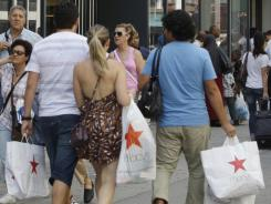 Shoppers pass H&M, in New York, Aug. 4.  Consumers spent more on autos, furniture and gasoline in July.