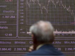 A broker looks on in front of the main screen at the Stock Exchange in Madrid on Aug. 9, 2011.