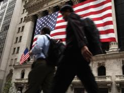 Pedestrians walk by the New York Stock Exchange on Monday.