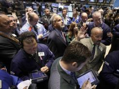 Specialist Daniel O'Donnell, right center, calls out prices at a post on the floor of the New York Stock Exchange Tuesday, Aug. 16, 2011.