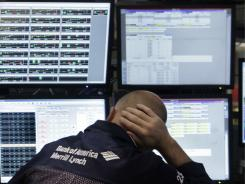 Specialist Michael O'Connor works at his post on the floor of the New York Stock Exchange, Friday Aug. 19, 2011.
