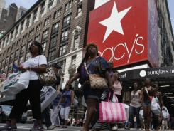 Shoppers pass Macy's  department store on Aug. 4  in New York.