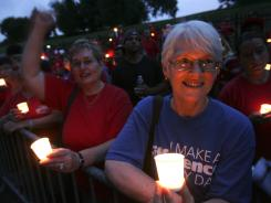 Diedre Rawson, left, and Cathy Stanford, right, both of Hamilton, join other striking Verizon workers picketing and holding a candle light vigil at the home of Verizon CEO Lowell McAdam in Mendham, N.J., on Thursday.