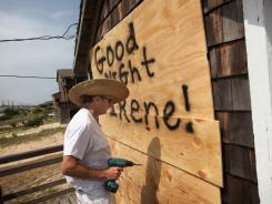 Fen Rascoe boards up his parent's cottage as they prepare for Hurricane Irene in Nags Head, N.C.