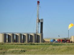 Natural gas is burned off next to an oil well Aug. 23 near Tioga, N.D.