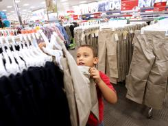 Elijah Goeddell, 8, of Lake Worth, Fla., looks for pants in the 'back to school' uniform department at Target in Greenacres.