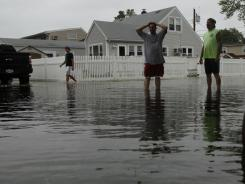 Residents examine the flooded streets Sunday of Wantagh, N.Y., after the remnants of Hurricane Irene passed through.