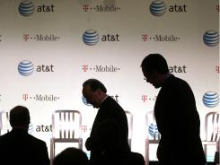 In this file photo, executives at AT&T attend a news conference in March where it was announced that AT&T planned to buy wireless rival T-Mobile USA.