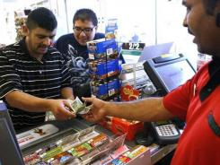 J.P Sira, right, owner of a 7-Eleven store in Palm Springs, Calif., sells scratch-off lottery tickets to Jose Gonzalez, left, and Jesus Leon on Aug. 5.