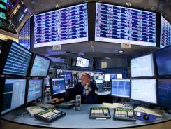 A trader works at his newly renovated post on the floor of the New York Stock Exchange Friday in New York.