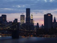 The Brooklyn Bridge, foreground, and the lower Manhattan skyline, with cranes atop the rising One World Trade Center.