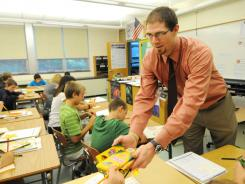 Lee Walter hands out colored pencils during his first day as a full-time teacher at Brandywine Heights Middle School in Topton, Pa.