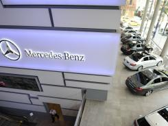 Company-owned Mercedes-Benz Manhattan has a video wall and a service bay visible from the showroom.