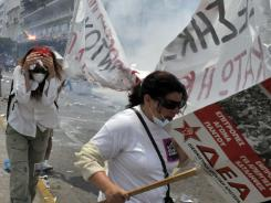 Protesters run from tear gas and riot police outside the Greek Parliament in Athens during a 48-hour general strike on June 29.