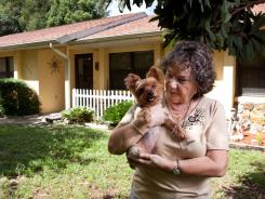 Nelly Rush stands in front of her Inverness, Fla., home, holding her Yorkie named &quot;Cricket&quot;.  Rush and her husband took out a reverse mortgage in 2006 but were shocked to find out that they owed $11,000 in closing cost fees.