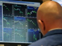 A number of indices show downward trends on the screen of this trader on the floor of the New York Stock Exchange,