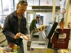 Actor Tom Amandes takes his groceries through the self service checkout aisle at a California grocery store in this file photo.