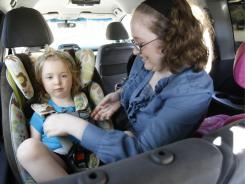Anne Hamilton, a mother of three, buckles her 3-year-old daughter Maggie into the car seat in her mini van in Tujunga, Calif.