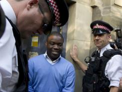 Kweku Adoboli, center, walks to a security van after appearing at the City of London Magistrates Court in London, Sept. 16, 2011.