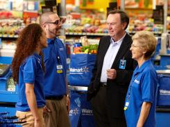 Wal-Mart Stores CEO Mike Duke, second from right, visits with workers at the retailer's Rogers, Ark., store.